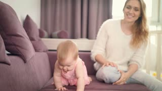 Little baby crawling on home sofa. Beautiful child crawling on bed. Sweet baby crawling away. Cute kid walking on all fours. Baby in pink dress learning creep