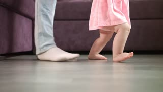 Little baby feet walking on floor with parent support. Close up of mother learning child walking. Kid feet steps at home. Little child learn to walking. Baby steps with mom. Toddler doing first step