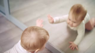 Little baby playing with mirror. Close up of cute kid looking mirror. Happy child reflection in mirror. Infant baby emotion. Cute child playing home