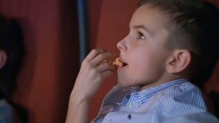 Little boy eating popcorn in cinema. Close up of boy face eating caramel popcorn at cinema. Young boy eating popcorn in slow motion. Teenager enjoy cinema food. Child eat cinema snacks