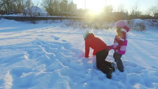 Little girl piggybacking mother in slow motion. Mother playing with daughter in sunny winter park. Happy winter fun on snow