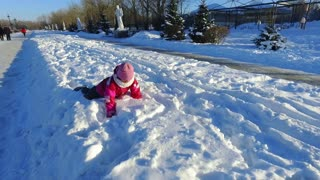 Little girl playing on snow in slow motion. Child having fun outdoors in winter. Carefree kid playing in snow. Happy wintertime
