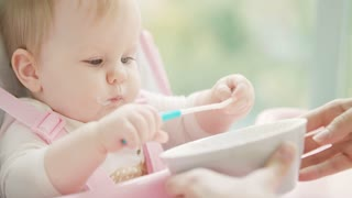 Little girl playing with spoon. Baby eating spoon. Portrait of little kid in baby chair gnawing spoon from bowl. Close up of cute infant eating by herself