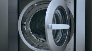 Loading washing machine. Load clothes to washer machine. Female hand put uniform in laundry machine. Load clothes laundry washing machine. Preparing laundry washing