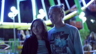 Love couple in amusement park at night. Close up of hipster couple looking at amusement at evening time. Youth having fun at night park