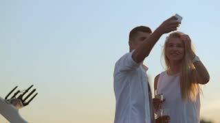 Love couple taking selfie. Attractive young woman and handsome man making selfie. Smiling and looking at camera. Honeymoon romantic couple in love