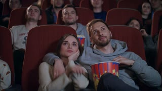 Love couple watching movie in cinema theatre. Couple in love embracing in cinema. People enjoying film and eating popcorn at cinema. Movie entertainment