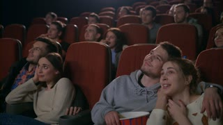 Love couples watching movie at movie theater. Guy feeding girl with popcorn at cinema theatre in slow motion. Young people eating popcorn and watching movie. Young couples embracing in cinema