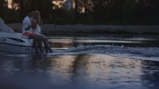 Lovely couple drinking champagne on floating motor boat. Luxury vacation. Romantic date on river in evening. Love couple enjoying cruising on motor yacht. Romantic relationship concept