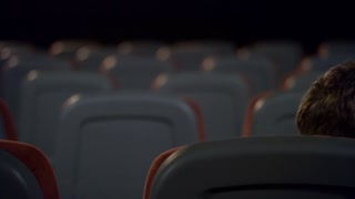 Loving couple kissing in back seats in cinema in slow motion. Young couple alone at empty theater. Romantic love couple kissing in movie theatre. Romantic cinema date