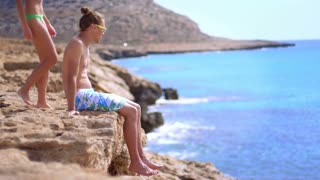 Loving couple resting at rocky cliff of sea. Girl joining her boyfriend on rocky seashore in slow motion. Guy enjoying ocean view together with girlfriend. Man and woman relaxing at Cyprus beach