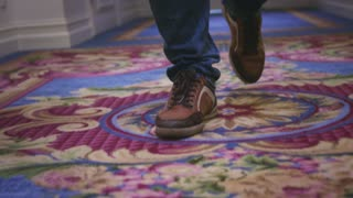 Male feet in sport shoes walking on carpet floor in corridor guest hotel. Close up man legs walking on long hallway in luxury mansion