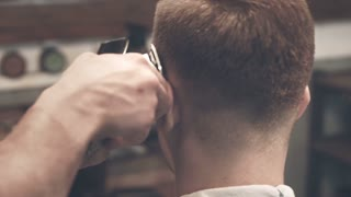 Male haircut. Male hairstyle. Close up of man hair cut. Male hands barber shaving man with electric razor in barbershop. Barber cutting hair with hairtrimmer