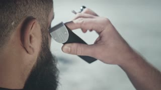 Male haircut outside. Close up of barber cutting man using hair clipper. Male grooming electric trimmer. Man hairstyle with electrical shaver. Beard cut. Beard styling with electric razor