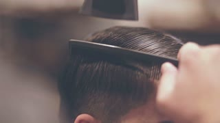 Male hairdressing. Drying hair man. Male hairstyling. Close up of male hair style. Hairdresser blowing hair man. Hairstyle man. Combing hair with dryer