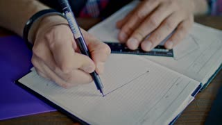 Male hands drawing sketch in notebook. Man using ruler and pencil for sketch drawing. Close up sketch drawing in notebook. Designer working on new product