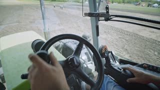 Male hands farmer driver on steering wheel combine harvest on agricultural field. View from inside tractor driver turns steering wheel agricultural machine