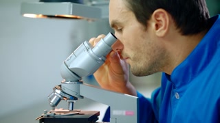 Male researcher working with microscope. Close up of lab researcher looking in microscope. Medical researcher doing microscope research. Research medical microscope