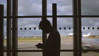 Male silhouette at airport window. Man watching departure of airplane from airport window. Silhouette standing at airport window. Male passenger looking departing plane