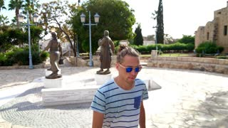 Male tourist walking at tropical city. Hipster man in sunglasses walking outdoor. Stylish traveler enjoy summer walk in town street. Guy in sunglasses going outside in sunny weather