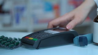 Man buy medicaments with card terminal at pharmacy. Close up of male hand swiping credit card on pay terminal at drugstore. Male customer using pos terminal at medical store