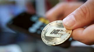 Man calculating profit from cryptocurrency mining on smartphone. Man holding gold altcoin in hand. Virtual cryptocurrency wallet. Investment in dashcoin. Global blockchain technology