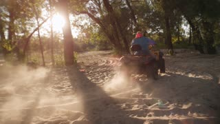 Man driving atv on sand in forest at sunset. Extreme male hobby. Man driving quad bike on sandy road in park. Guy driving off road atv on dry sandy road. Extreme lifestyle