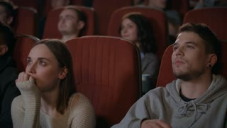 Man embracing woman in cinema theater. Romantic date concept. Close up of romantic couple watching film in movie theatre