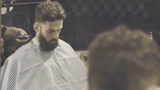 Man haircut. Beard man in barber shop. Hipster barbershop. Professional hairdresser cutting hair with electric hairclipper. Beard man cutting hair. Man hair model