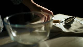 Man hand pours flour through sieve into glass bowl. Close up sifting flour through sieve. Pour flour into bowl. Flour sifter. Preparation of ingredients for baking. Food ingredient
