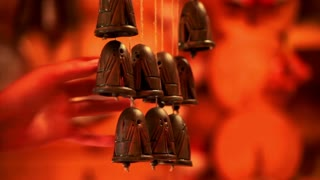 Man hand touching ceramic bells. Ceramic bells pendant chimes wind music on red background. Close up touch clay bells wind music. Ethnic ceramic bells sound wind slowly swinging
