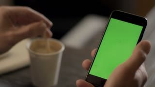 Man holding mobile smart phone in hand with chroma key green screen. Smartphone with green background on screen. Mobile lifestyle concept. Close up of male hand holding coffee cup and mobile