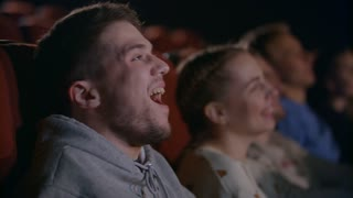 Man laughing at comedy film. Close up of spectators of cinema have fun in slow motion. Male emotion at movie entertainment