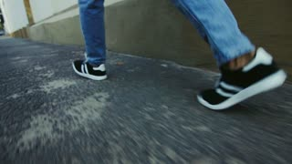 Man legs walking on street. Guy in sneakers going on asphalt city sidewalk. Close up of man legs in blue jeans and sport shoes quickly walking in city. Casual clothes style for outdoor urban life