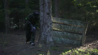 Man player in paintball game with gun running on shooting range slow motion. Paintball team attacking enemy on battle field during shooting game in forest
