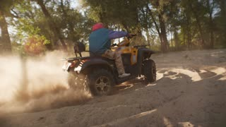 Man riding atv on sand picking up pillar of dust at sunset. Modern guy driving quadbike at extreme holiday. Tourist man driving quad bike on sand in slow motion. Extreme driving sports at forest