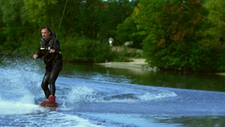 Man riding board on waves of river. Wake boarding rider training on wakeboard boat in slow motion. Young sport man water skiing. Extreme water sports