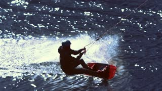 Man riding on wakeboard and falling into water in slow motion. Training in surfing. Athletic man after trick with jump on wakeboard plunging into water. Waterskier in action. Extreme water sports