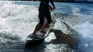 Man riding surf on waves of river. Close up of wake surfing rider training on waves in slow motion. Extreme water sports. Wakesurfing sport