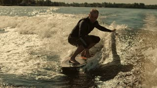 Man surfing on waves in slow motion. Wake surfing rider enjoy waves. Close up of extreme rider on wakesurf board