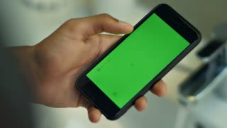 Man touching smartphone with chroma key green screen. Close up of smart phone with green screen in male hand. Mobile phone with green screen in human hands. Modern technologies in action
