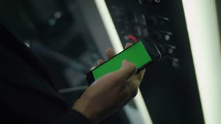 Man using smartphone with chroma key green screen during staying in elevator. Close up of mobile phone with chroma key in male hand. Man touching mobile smart phone with chroma key green screen