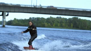 Man wakeboarding on river waves under city bridge in slow motion. Rider going fast on wakeboard on river. Extreme sportive hobby. Extreme vacation in movement. Rider on wake board enjoy wave