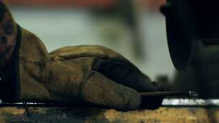 Mechanic cutting metal with grinder in factory. Heavy industry metalworking in workshop. Close-up of sparks while grinding iron. Craftsman in construction gloves working with electric tool
