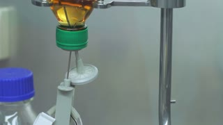 Medical dropper bottle with orange liquid. Close up of chemical liquid injection from glass bottle. Chemical reagent in drop counter. Laboratory research process