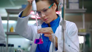 Medical researcher in lab. Medical scientist working with liquid in lab flask. Laboratory technician in research lab. Female researcher pouring reagent in lab flask with micropipette