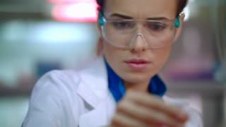 Medical researcher in medical lab. Close up of female lab researcher doing medical research. Woman scientist. Pharmaceutical research. Medical scientist doing laboratory research. Liquid in lab flask