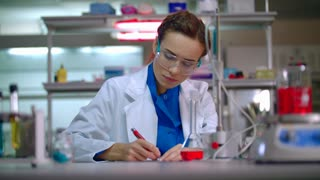 Medical scientist in lab. Woman scientist analyzing liquid sample. Lab worker bring test tube rack in medical lab. Lab worker help woman scientist. Chemist working in pharmaceutical laboratory