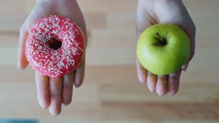 Menu choosing between fresh green apple or donut. Close up woman hands holding apple and doughnut. Top view healthy or unhealthy food. Healthy natural fruit or sweet dessert nutrition