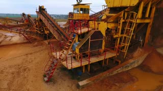 Mining equipment at sand mine territory. Sky view of mining equipment working at sandpit. Industrial machinery. Sand mining at quarry. Aerial view of mining conveyor at sand quarry